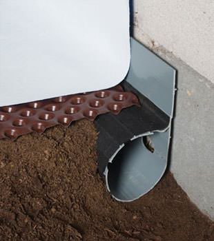 Closeup of a crawl space drainage system installed in New Bedford